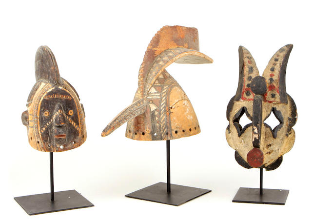 Three African masks height of largest 11in; width 18 1/2in; depth 6 1/2in
