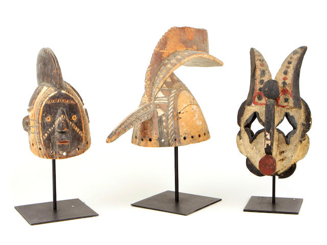 Three African masks including: A Mossi Tribe helmet mask with human face, A Bobo Mossi tribe helmet mask, A Nigerian Ogoni Tribe mask.