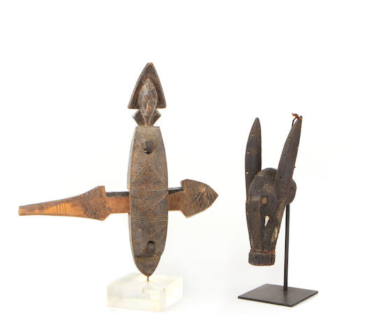 Carved wood door lock: African, Bambara Tribe; lock surmounted by male head with triangulated head dress (base included) An African marionette mule head: Bambara Tribe ebony ground with surface incising.