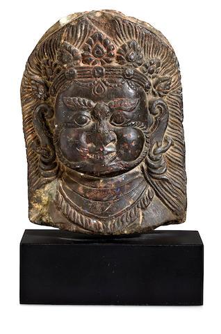 A stone Mahakala face panel Tibet, 18th century