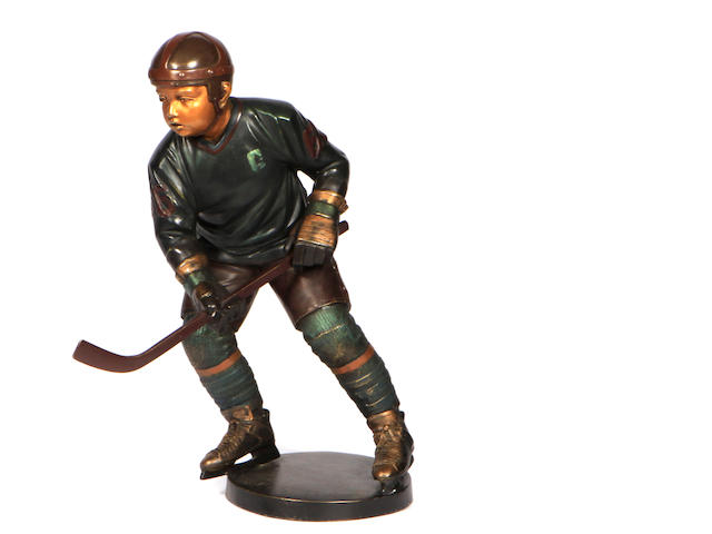 A cold painted bronze figure of a hockey player