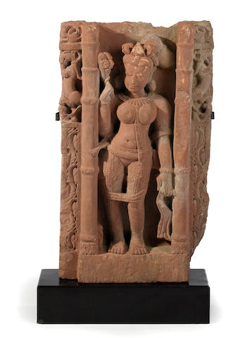 A red sandstone carving of a female attendant
