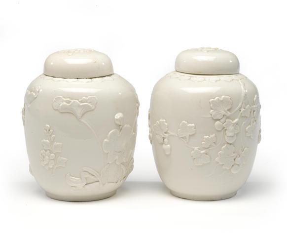 A pair of molded and white-glazed ginger jars with flower design in relief With cover, stamped China height 9 ¼in