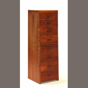 A mixed wood tall chest of drawers