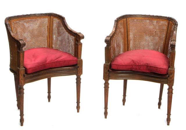 A pair of Louis XVI style carved beechwood and cane paneled tub armchairs