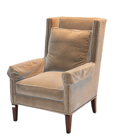 A contemporary velvet upholstered wing chair