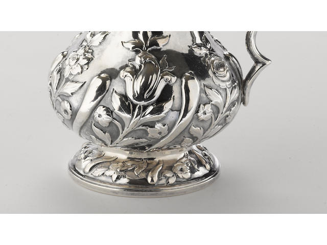 A silver cream pitcher with spiral fluted and floral chased decoration by Bennett & Caldwell, Philadelphia, PA, circa 1843-1848 <BR />Monogrammed: EK