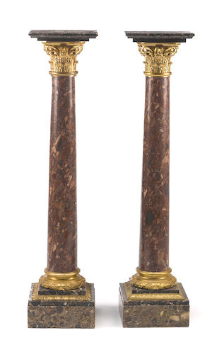 A pair of Louis XVI style gilt bronze mounted variegated red and black marble columnar pedestals<BR />late 19th century
