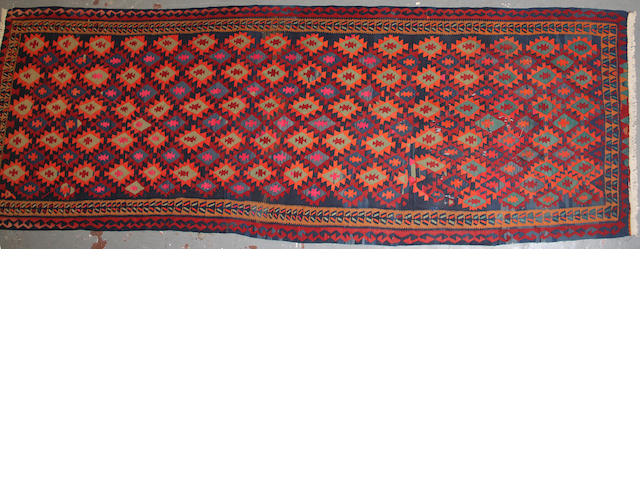 A Persian kilim size approximately 5ft. 6in. x 15ft. 8in.