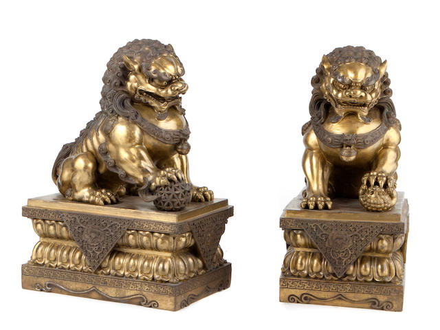 A pair of Chinese bronze models of Fu dogs