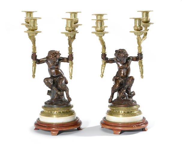 A pair of Louis XVI style gilt and patinated bronze figural four light candelabra<BR />after models by Claude Michel called Clodion (French, 1738-1814)<BR />20th century