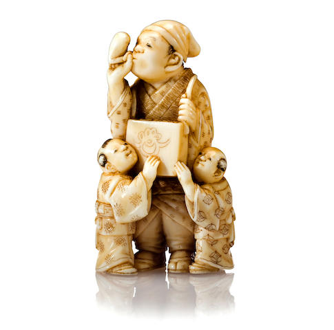An ivory netsuke of a candy vendor By Tomomasa, Edo period (19th century)