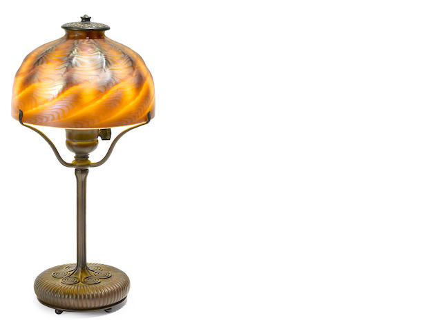 A Tiffany Studios favrile glass and bronze table lamp together with a Tiffany Lamps brochure