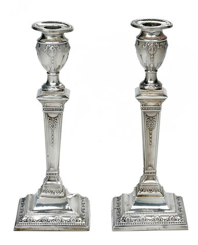 A pair of late Victorian Adam-style sterling silver candlesticks<BR />London, 1895, with double struk maker's marks