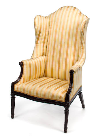 A George III upholstered wing armchair