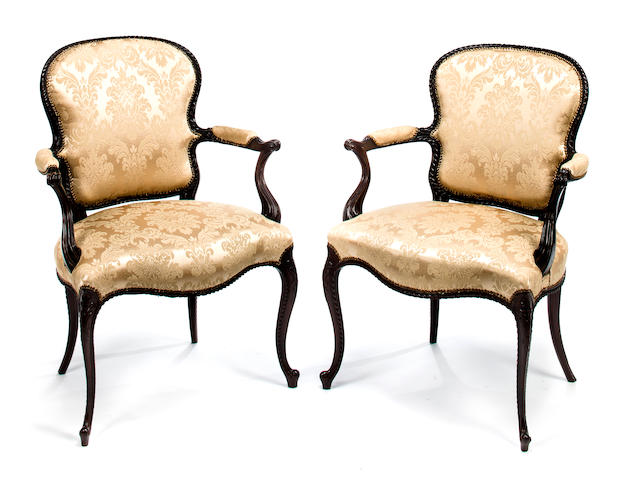 A pair of George III carved mahogany open armchairs in the French taste