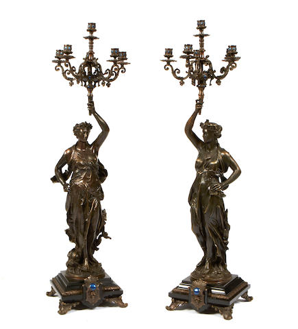 A pair of Louis XVI style patinated bronze six light candelabra