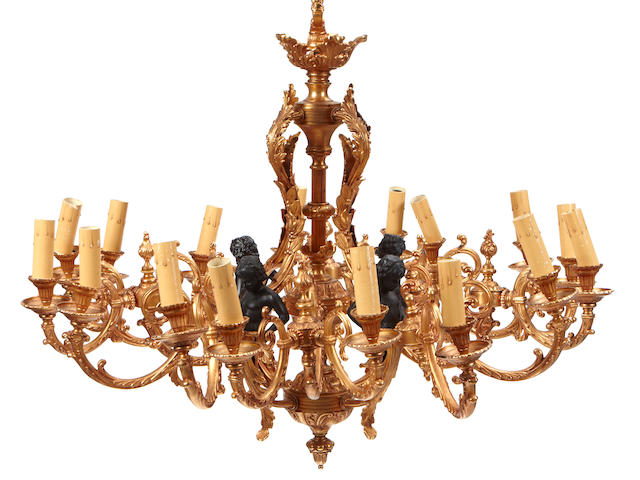 A Louis XV style parcel ebonized gilt bronze sixteen light chandelier