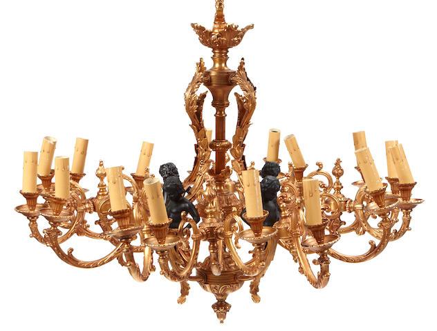 A Louis XV style parcel ebonized gilt bronze sixteen light chandelier