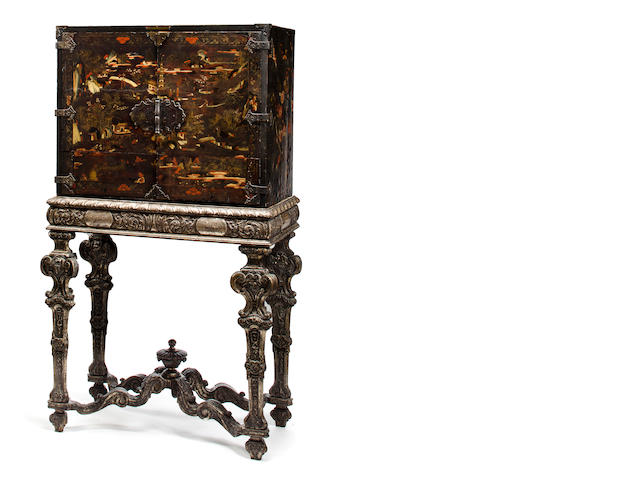 A George I lacquered and Chinoiserie decorated cabinet on later silvered wood stand<BR />the cabinet first quarter 18th century, the stand second half 19th century