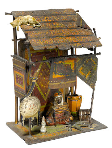 An Austrian cold painted bronze lamp of an Arab seated in a stall with a cat perched on the roof circa 1900