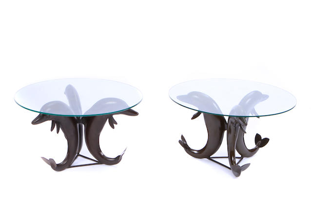 A pair of patinated bronze and glass dolphin form tables