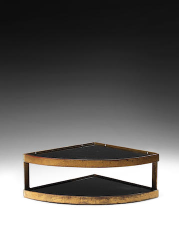 A gilded metal two tier triangular corner shelf with dark glass shelves  Royere