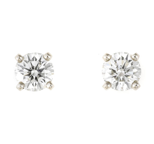 A pair of diamond and platinum solitaire earrings, De Beers, 2 diamonds = .84ct; with box and papers