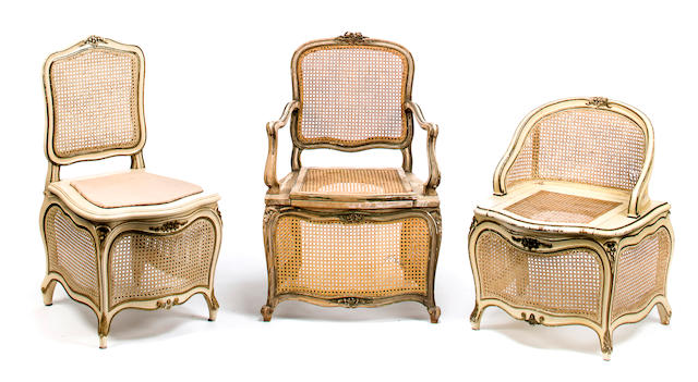 Three Louis XV style chaises percées, mid 20th c., cream painted and green highlighted wood and caning, h x w x d (largest): 37 ¾ x 20 ½ x 22in. (96 x 52 x 56cm)