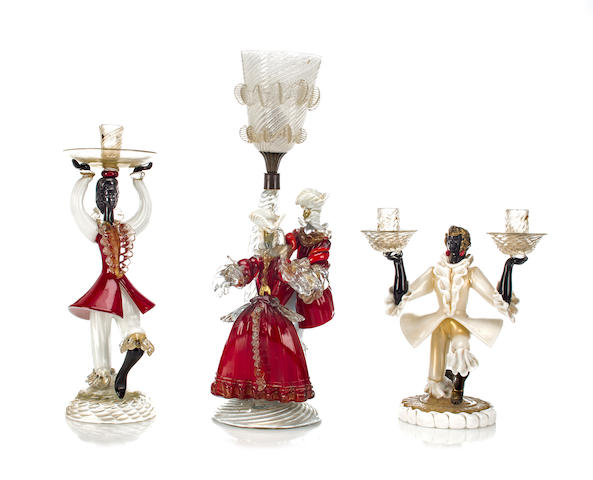 Group of three blackamoor lighting articles 	Murano, mid 20th c.  	colored, clear and gilt glass 	comprising: table lamp, two light candelabrum, candlestick 	h: from 11-19in. (28.5 x 48cm)