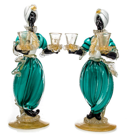 A pair of Blackamoor two light candelabra 	mid 20th c.  	colored glass 	h: 13 ½ in. (35cm)
