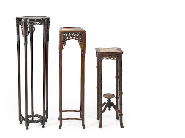 A group of three carved hardwood vase stands