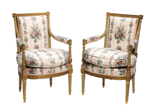 A set of four Louis XVI style paint decorated parcel gilt fauteuils