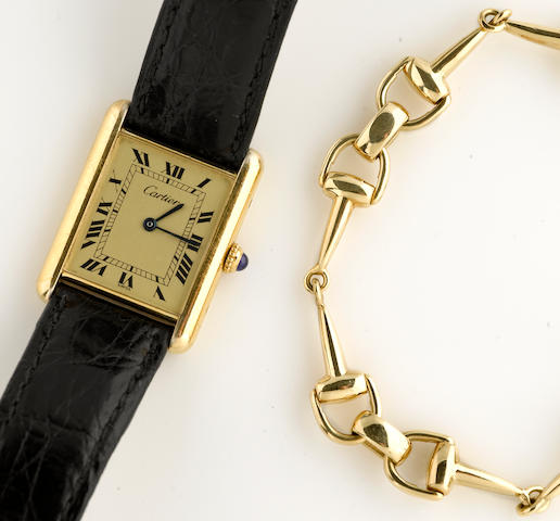 A gold-plated silver wristwatch with leather strap, Must de Cartier, together with an eighteen karat gold stirrup link bracelet