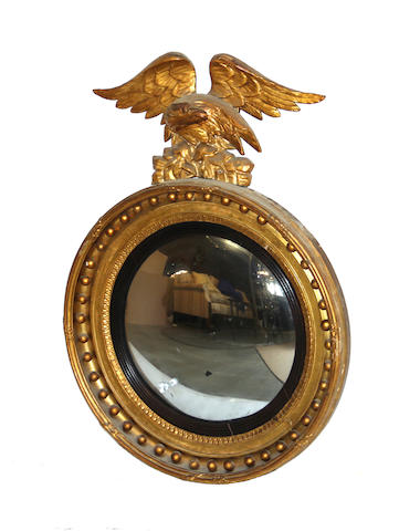 A Classical gilt wood convex mirror<BR />American or English<BR /> (Eagle finial possibly by association) early 19th century