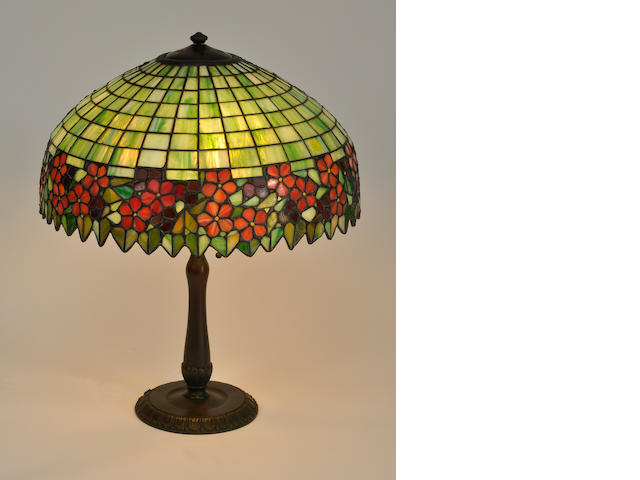 A leaded glass and patinated metal table lamp<BR />the shade attributed to Unique Art Glass, the base by Handel<BR />first quarter 20th century