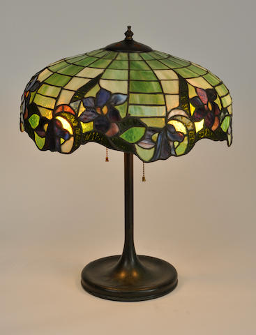 An American leaded glass and patinated metal floral table lamp<BR />the base by Handel<BR />first quarter 20th century