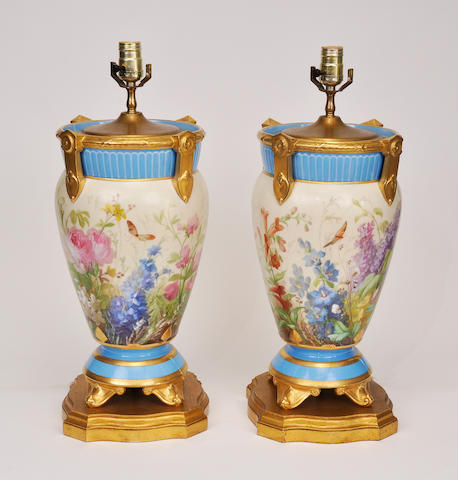 A pair of floral painted porcelain urns later mounted as table lamps<BR />20th century, probably French