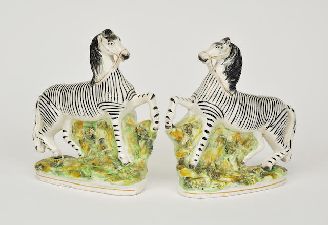 A pair of Staffordshire figures of zebras late 19th century