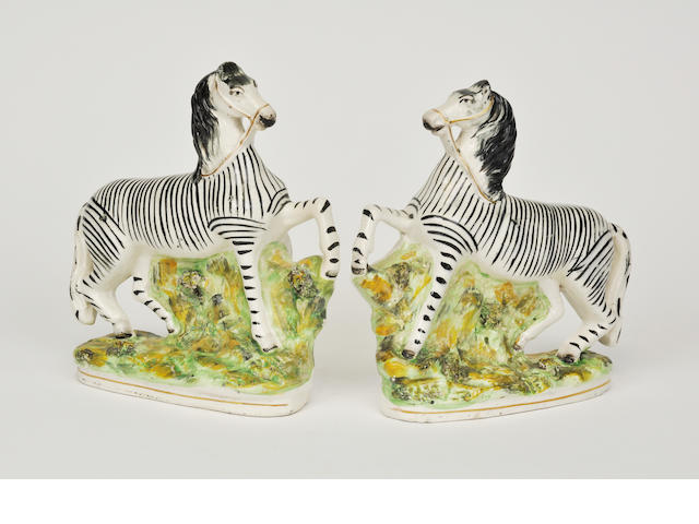 A pair of Staffordshire figures of zebras<BR />late 19th century