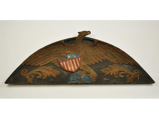 A carved and painted stern board of a wingspread eagle holding a shield