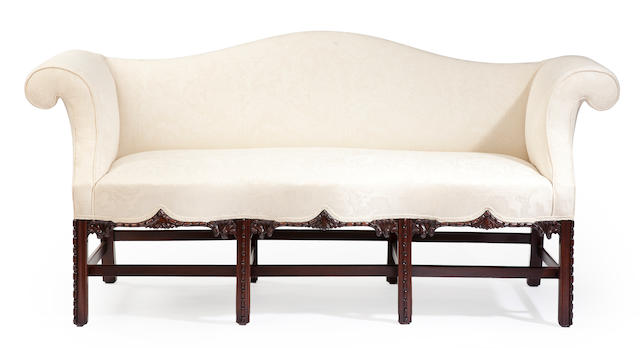 A group of Chippendale style mahogany furniture Consisting of an upholstered camel back sofa, pair of bergeres, pair of white leather upholstered wing chairs and ottomans, and pair of side chairs.