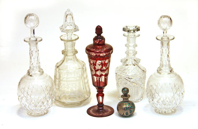 A Bohemian ruby glass pokal, four cut and engraved glass decanters and a silver overlay green glass scent bottle late 19th/early 20th century