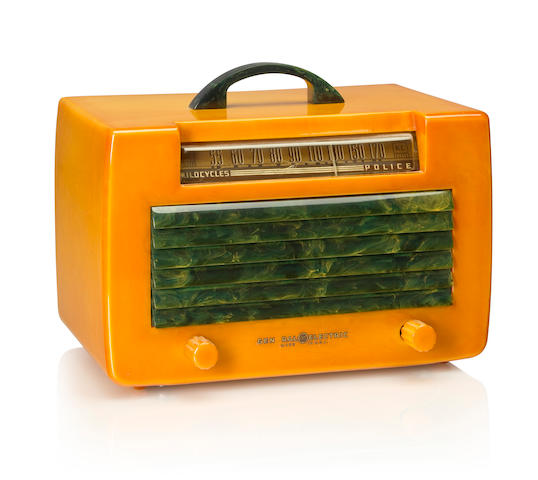 A General Electric L-570 1941 Yellow case with yellow knobs, blue handle and louvered grille, with General Electric decal. height 6 1/4in (15.4cm); length 9 1/2in (24.2cm); depth 6in (15.2cm)