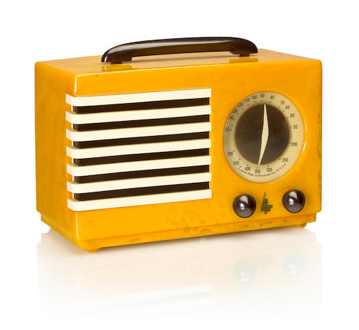 An Emerson 400 Aristocrat 1940 Yellow case with black handle, knobs and black and white grille. height 7 1/4in (18.5cm); length 10 7/8in (27.6cm); depth 5 3/8in (13.6cm)