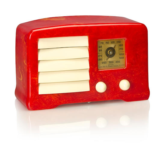 An Emerson AX235 Little Miracle 1938 Marbleized red case with white knobs and louvered grille. height 5 1/4in (13.4cm); length 8 7/8in (22.5cm); depth 3 3/4in (9.5cm)