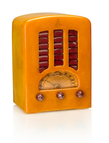 An Emerson BT245 Cathedral 1938 Mottled yellow case with maroon knobs and louvered grille, with Emerson decal. height 10in (25.5cm); width 7 1/4in (18.5cm); depth 5in (12.8cm)