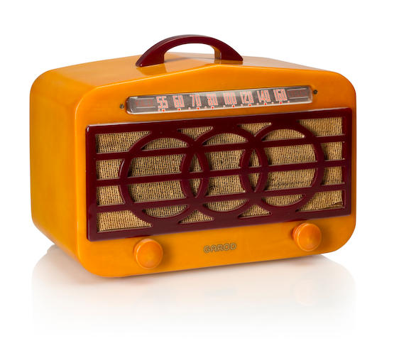 A Garod 126 Circle Grille 1940 Yellow case with maroon knobs, grille and handle, with Garod decal. height 7in (17.8cm); length 10 1/2in (26.8cm); depth 6in (15.2cm)