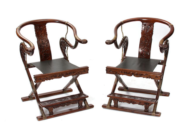 A pair of Chinese Ming style carved horseshoe back folding armchairs
