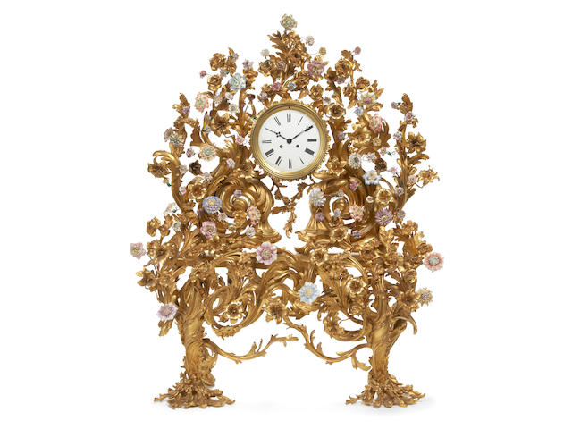 A monumental Louis XV style gilt bronze porcelain mounted mantel clock partially incorporating 19th century elements